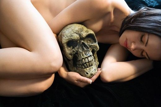 Nude Caucasian young adult woman lying down holding human skull. : Stock Photo