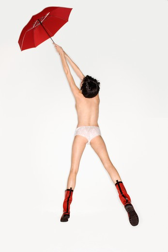 Young Caucasian woman in underwear and red boots floating into the air holding red umbrella. : Stock Photo