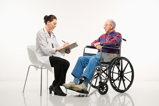Stock Photo: 4184R-7487 Mid-adult Caucasian female doctor taking notes with an elderly Caucasian male in wheelchair to her side.