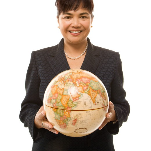 Filipino middle-aged businesswoman holding globe in both hands standing in front of white background. : Stock Photo