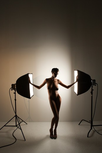 Nude African American mid adult woman standing between soft boxes in photography studio. : Stock Photo