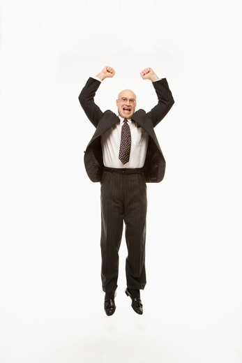 Smiling Caucasian middle-aged businessman jumping with arms raised. : Stock Photo