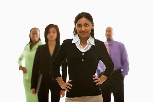Stock Photo: 4184R-7732 Portrait of Indian businesswoman smiling with hands on hips with others in background.