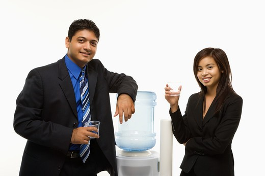 Vietnamese businesswoman and Indian standing at water cooler looking at viewer. : Stock Photo