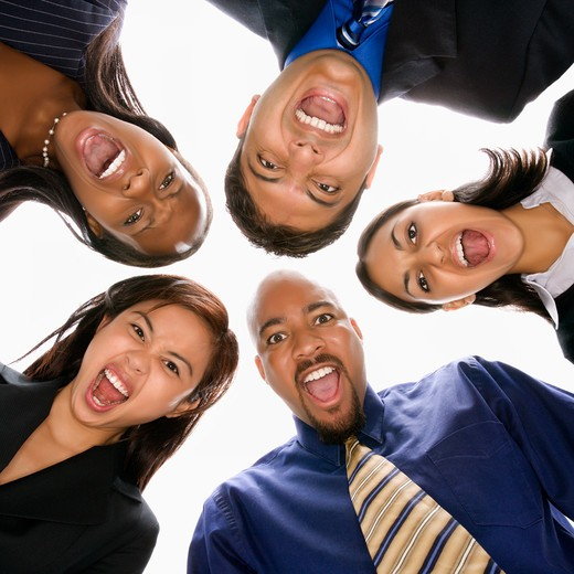 Low angle portrait  of multi-ethnic business group of men and women in huddle screaming. : Stock Photo