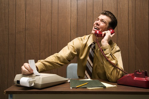 Caucasion mid-adult retro businessman sitting at desk talking on telephone using adding machine. : Stock Photo