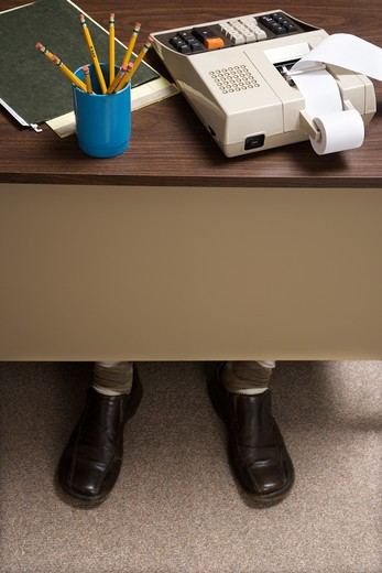 Feet of retro businessman sticking out of bottom of desk with notebook, pencils and adding machine. : Stock Photo