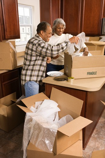 Middle-aged African-American couple packing moving boxes in kitchen. : Stock Photo