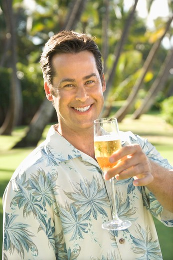 Caucasian mid adult man toasting viewer with champagne glass. : Stock Photo