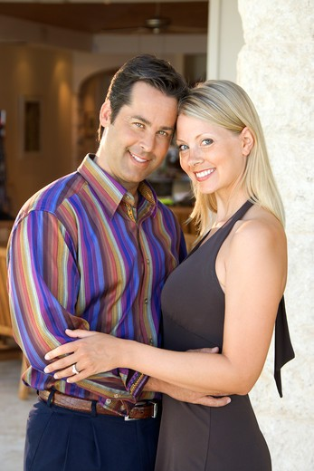 Stock Photo: 4184R-8380 Caucasian mid adult couple embracing and smiling at viewer.
