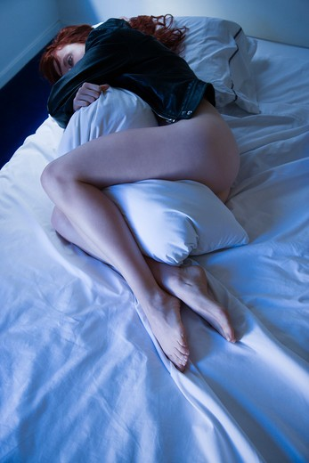 Stock Photo: 4184R-8581 Partially nude young redhead woman lying in bed hugging pillow.