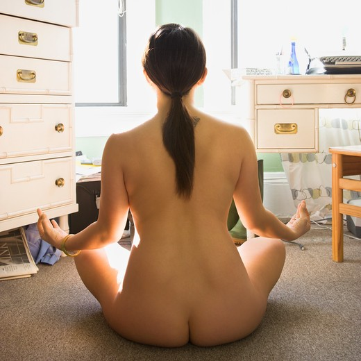 Back view of pretty nude Asian young woman sitting on floor meditating in lotus pose. : Stock Photo