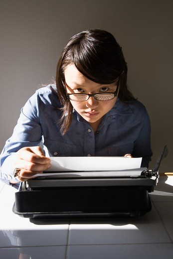 Pretty Asian young woman with typewriter making eye contact over glasses. : Stock Photo