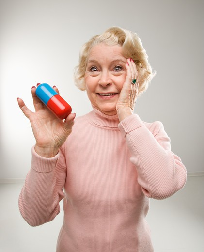 Stock Photo: 4184R-8986 Caucasian senior woman holding oversized pill at viewer.