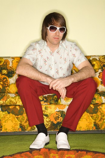 Stock Photo: 4184R-9092 Portrait of Caucasian mid-adult man wearing sunglasses sitting on colorful retro sofa.