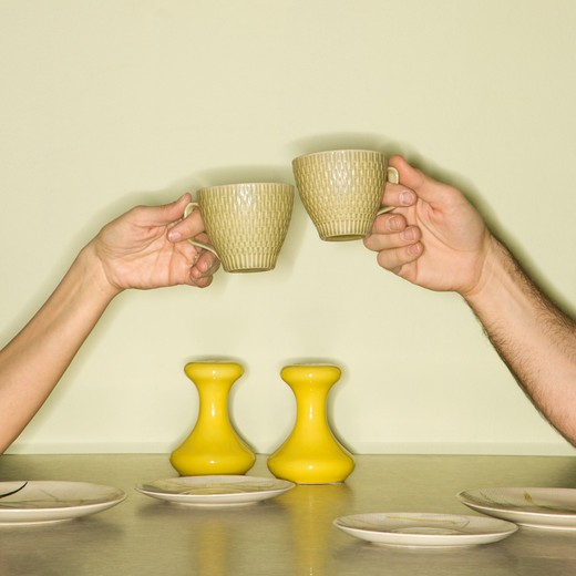 Caucasian mid-adult male and female hands toasting with coffee cups across retro kitchen table setting. : Stock Photo