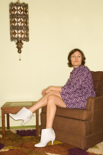 Pretty Caucasian mid-adult woman wearing vintage clothing sitting in brown retro chair looking bored. : Stock Photo