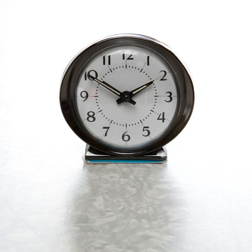 Still life of round vintage alarm clock on table. : Stock Photo