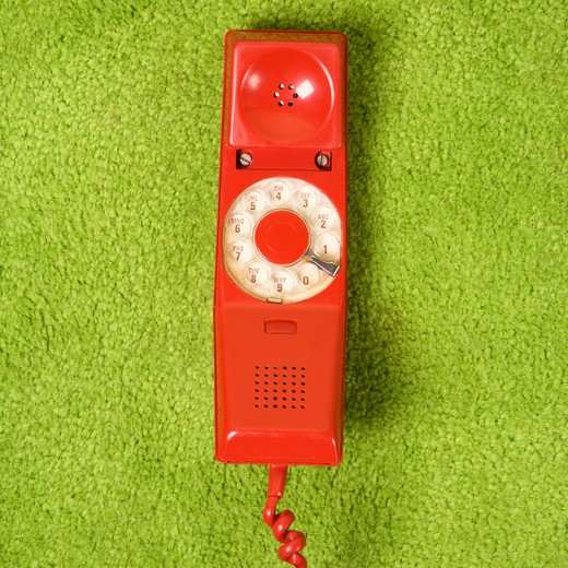 Red vintage rotary telephone receiver lying on 70's green carpet. : Stock Photo