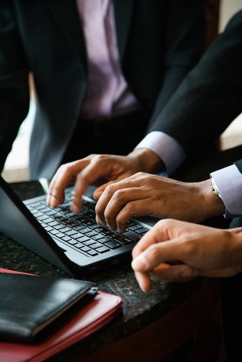 Cropped close-up of three business people and a laptop with the focus on hands typing in the foreground. Vertical format. : Stock Photo