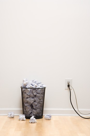 Full wire mesh trash can with crumpled paper next to electrical outlet and plugs. : Stock Photo