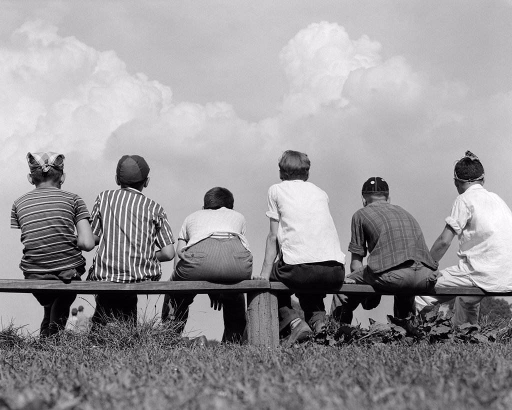 1960S Back View Of Six Boy Baseball Players Sitting On Bench : Stock Photo