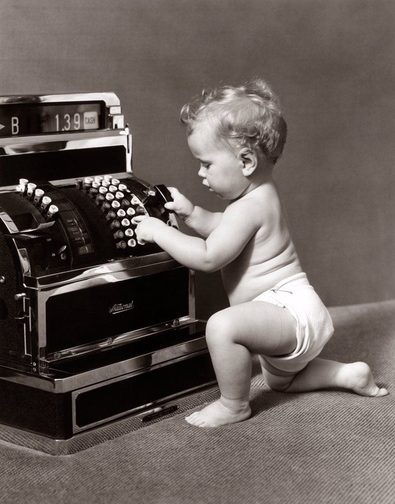 1930S 1940S Salesperson Baby Wearing Diaper Ringing Up Sale On Cash Register : Stock Photo