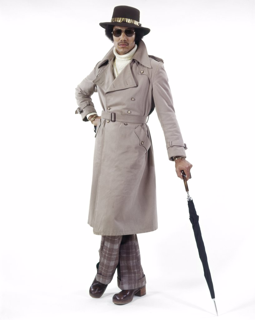 Stock Photo: 4186-11090 1970S Full Length Portrait Stylish African American Man Wearing Sunglasses Wide Brim Hat Trench Coat Leaning On Umbrella