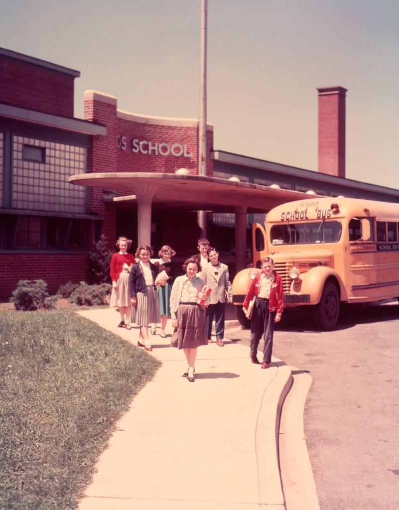 Stock Photo: 4186-11209 1950S Group Elementary School Kids Boys Girls Walking Away Bus Building Sidewalk Education