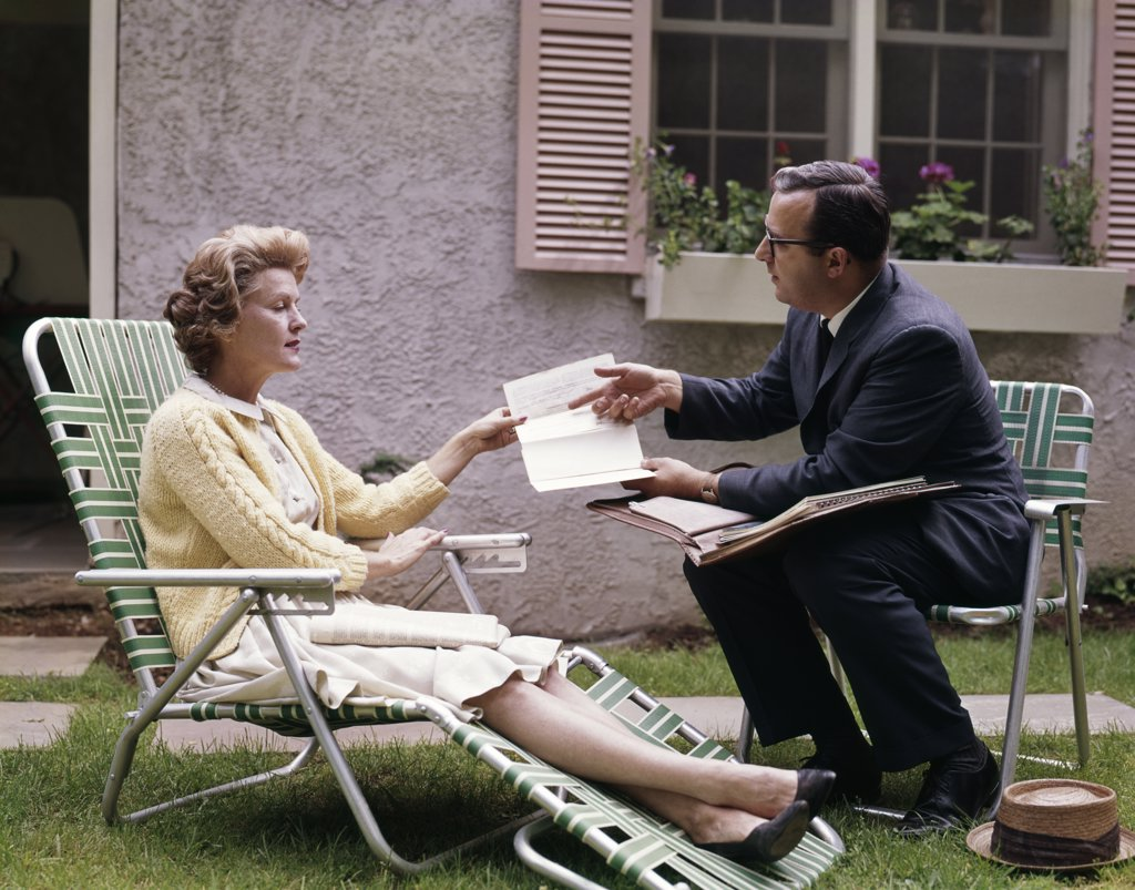 Stock Photo: 4186-11360 1960S Man Showing Material In Papers To Woman Sitting Outside Suburban House Insurance Medical Salesman