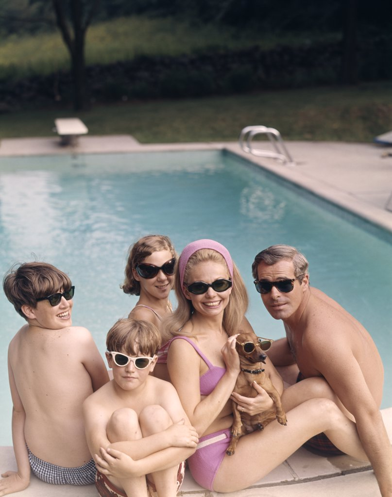 Stock Photo: 4186-11417 1960S 1970S Family All Wearing Sunglasses Beside Swimming Pool