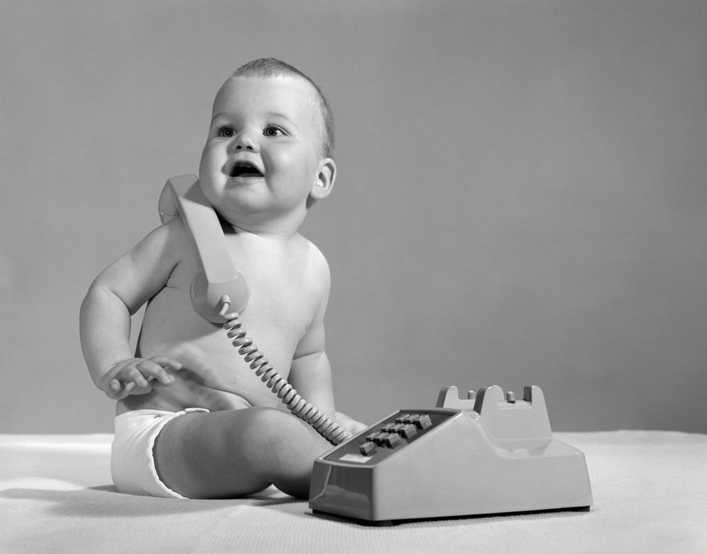 Stock Photo: 4186-1143 1960S 1970S Smiling Baby In Diaper With Telephone