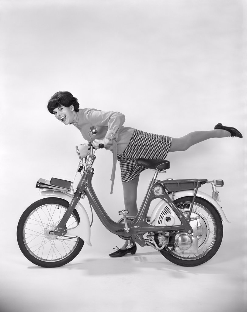 1960S 1970S Young Woman Smiling Getting On Motor Bike Or Moped With Her Leg Extended Over Back Of Bike : Stock Photo