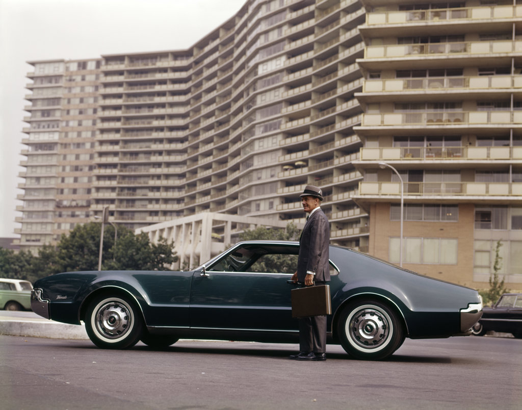 Stock Photo: 4186-11710 1970S Salesman With Attaché Case Standing Beside Car Outside Apartment Condominium Building