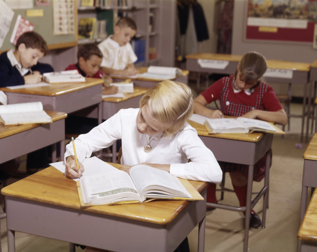 Stock Photo: 4186-11731 1960S Elementary School Children In Classroom At Desks Working With Books And Papers Boy Girl