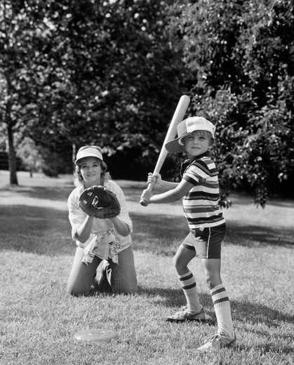 Stock Photo: 4186-1209 1980S Boy At Bat With Mother Kneeling Behind Him As Catcher