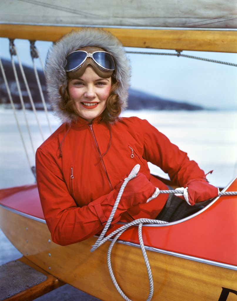 1940S Smiling Young Woman Wearing Gloves Fur Hat Goggles Sitting In Cockpit Of Ice Boat Holding Sheet Rope To Sail Boom : Stock Photo