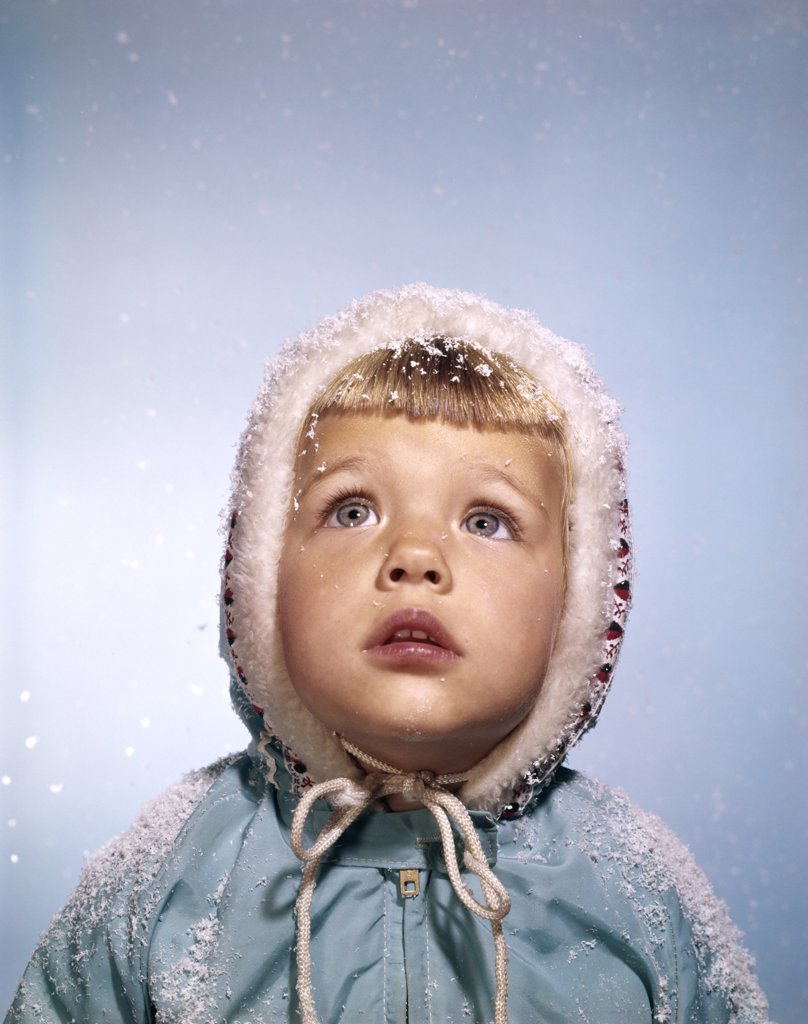 Stock Photo: 4186-12253 1960S Cold Little Blond Girl In Winter Coat And Hood Looking Up At Falling Snow