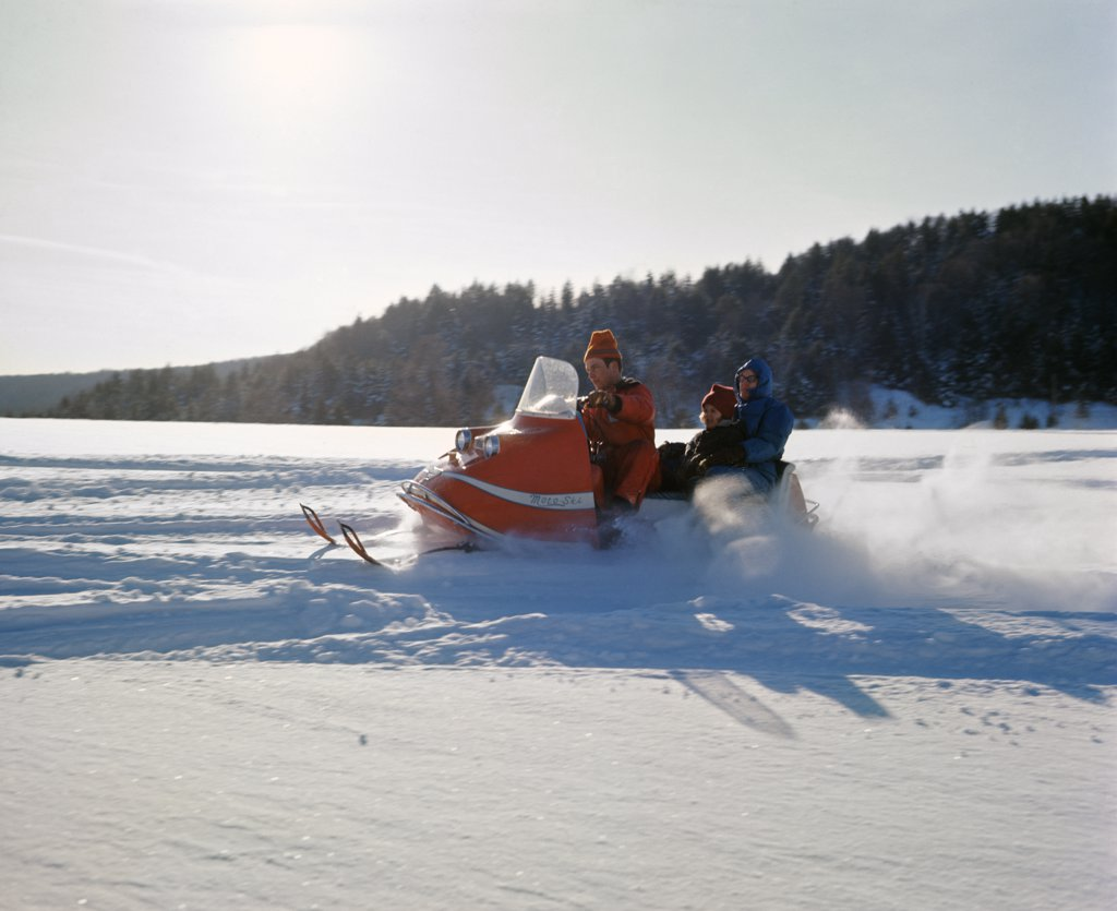 1960S Family Riding On Snowmobile In Snowy Winter Landscape : Stock Photo