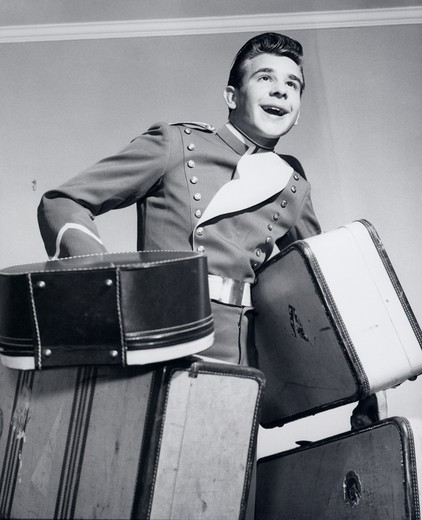 Stock Photo: 4186-1234 1950S Smiling Bellboy Carrying Four Bags Of Luggage