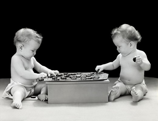 Stock Photo: 4186-1244 1930S 1940S Twin Babies Playing Game Of Checkers Together Studio