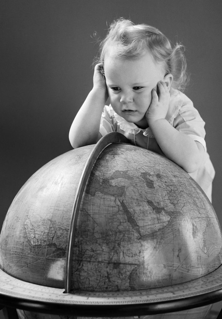 1940S Baby Looking At Leaning On Globe Of Earth : Stock Photo