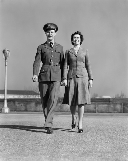 1940S Smiling Couple Walking Forward Man In Army Uniform : Stock Photo