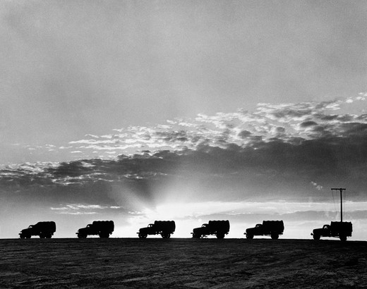 Stock Photo: 4186-13043 1940S Line Of Military Trucks At Sunset