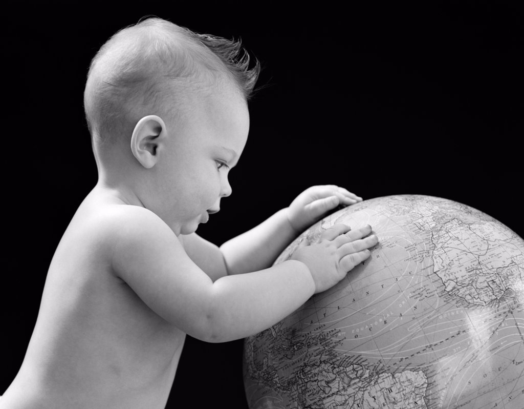 1940S Baby With Hands On Globe Looking At The Earth : Stock Photo