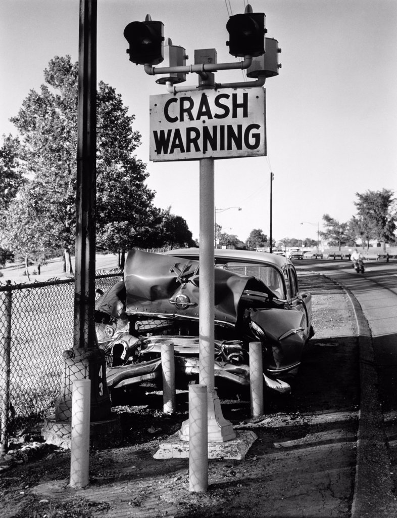 Stock Photo: 4186-13249 1950S Car Crashed Head-On Into Crash Warning Sign Pole Symbolic Outdoor
