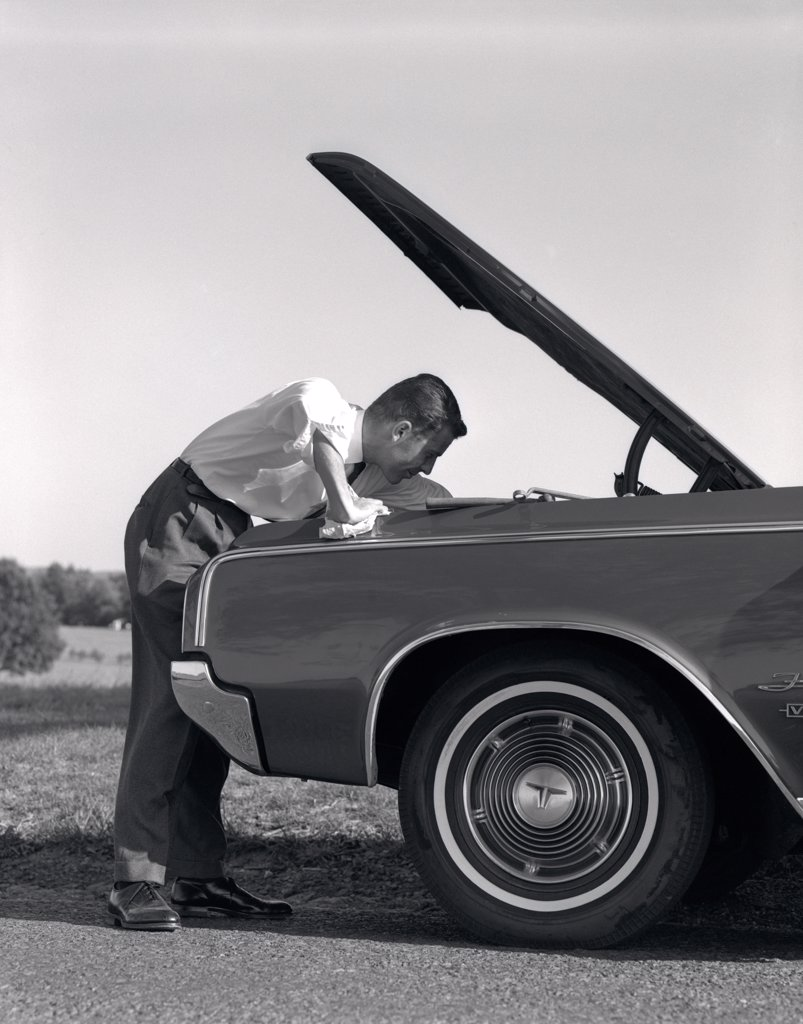 Stock Photo: 4186-13310 1960S Side View Of Man In Shirt & Tie Looking Under Hood Of Car Pulled Up On Side Of Road