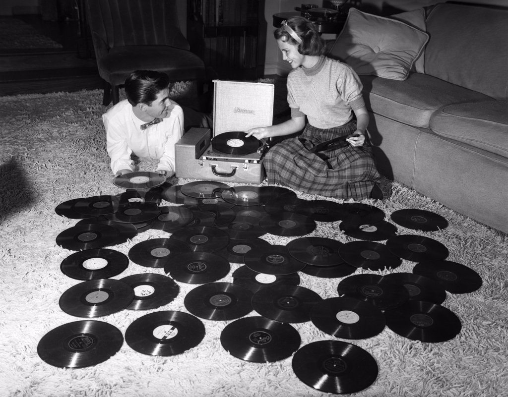 1950S Teenage Couple Playing Many Music Records Spread Out On Living Room Floor : Stock Photo