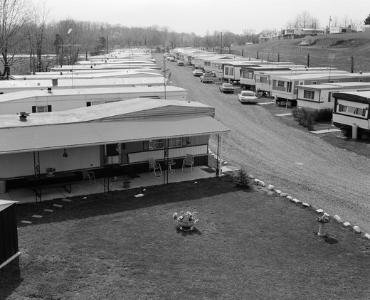 1970S Trailer Park With Rows Of Mobile Homes On Either Side Of Gravel Road : Stock Photo