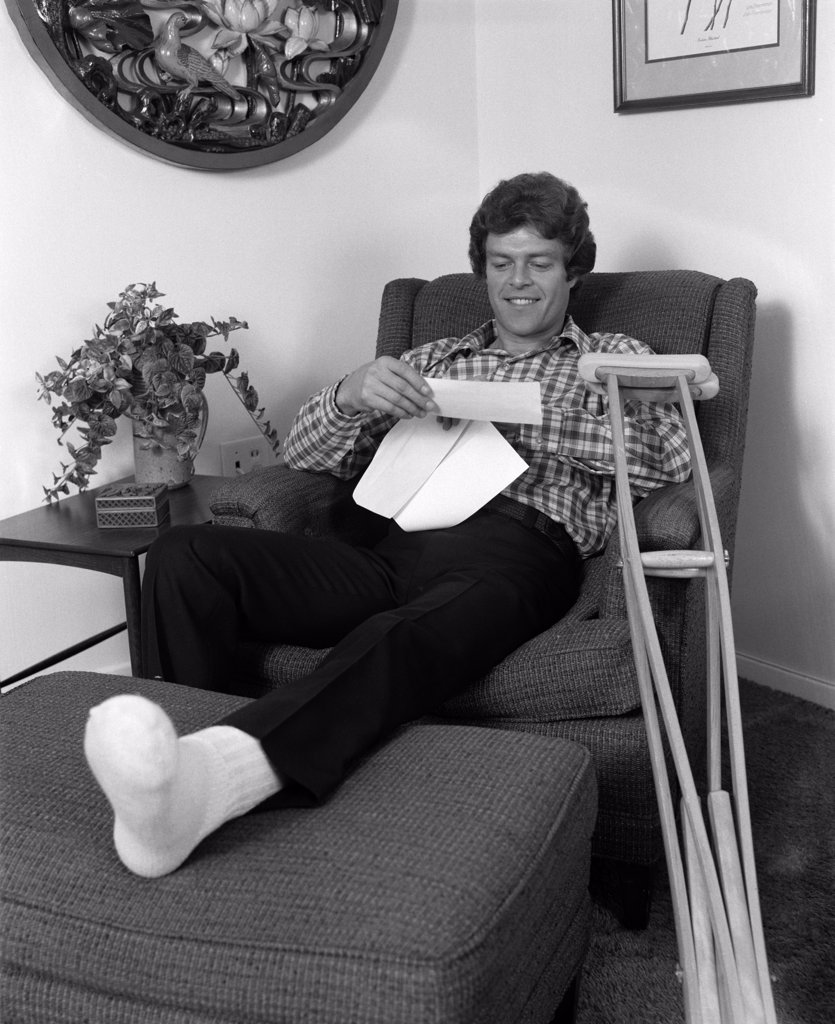 1970S Young Man In Arm Chair With One Leg Propped Up Crutches Nearby Reading A Letter Indoor : Stock Photo